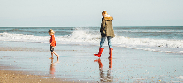 Young-family-walking-on-the-beach-